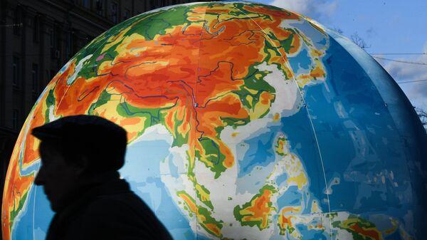 Человек на фоне глобуса. Архивное фото